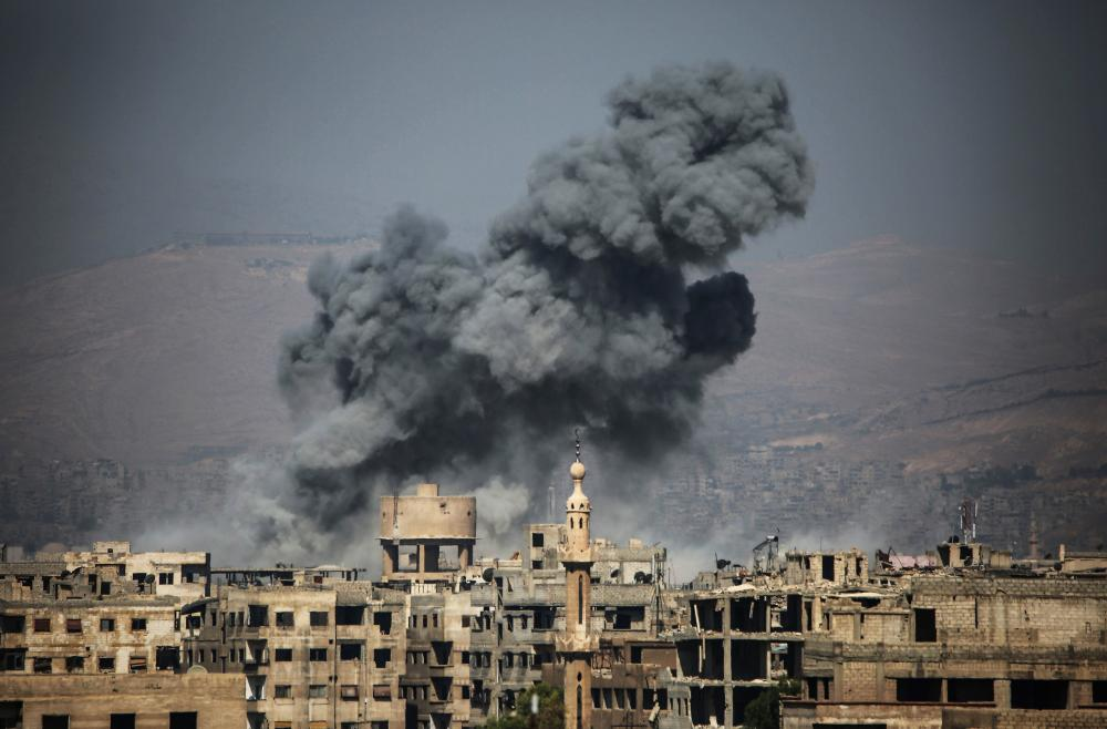 Smoke rises from buildings following a reported air strike on the rebel-held town of Ayn Tarma, in Syria's eastern Ghouta area. — AFP