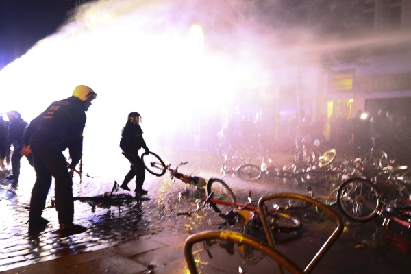 Riot police officer pulls a bicycle that protesters used as a barricade during demonstrations at the G20 summit in Hamburg, Germany, on Sunday. — Reuters