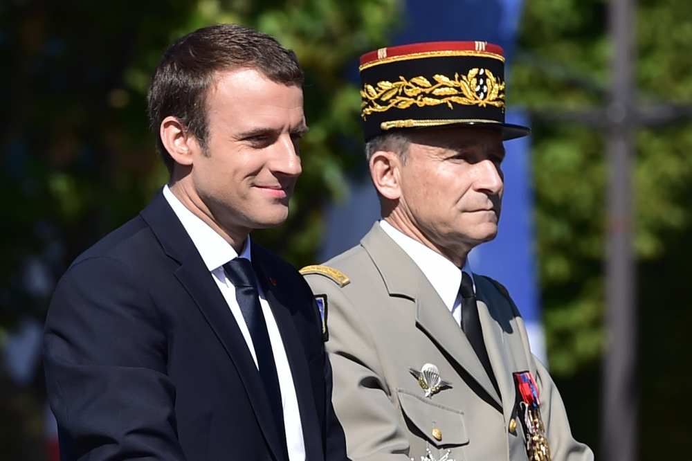 French President Emmanuel Macron (L) and Chief of the Defence Staff, French Army Gen. Pierre de Villiers ride aboard a command car during the annual Bastille Day military parade on the Champs-Elysees avenue in Paris on Friday. The parade on Paris's Champs-Elysees will commemorate the centenary of the US entering WWI and will feature horses, helicopters, planes and troops. — AFP