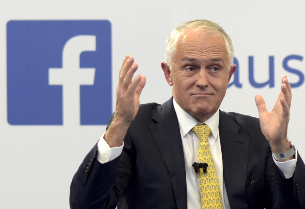 In this file photo, Australian Prime Minister Malcolm Turnbull raises his hands as he speaks during a leaders debate hosted by Facebook Australia and News.com.au in Sydney. The Australian government on Friday proposed a new cybersecurity law to force global technology companies such as Facebook and Google to help police by unscrambling encrypted messages sent by suspected extremists and other criminals. — AP