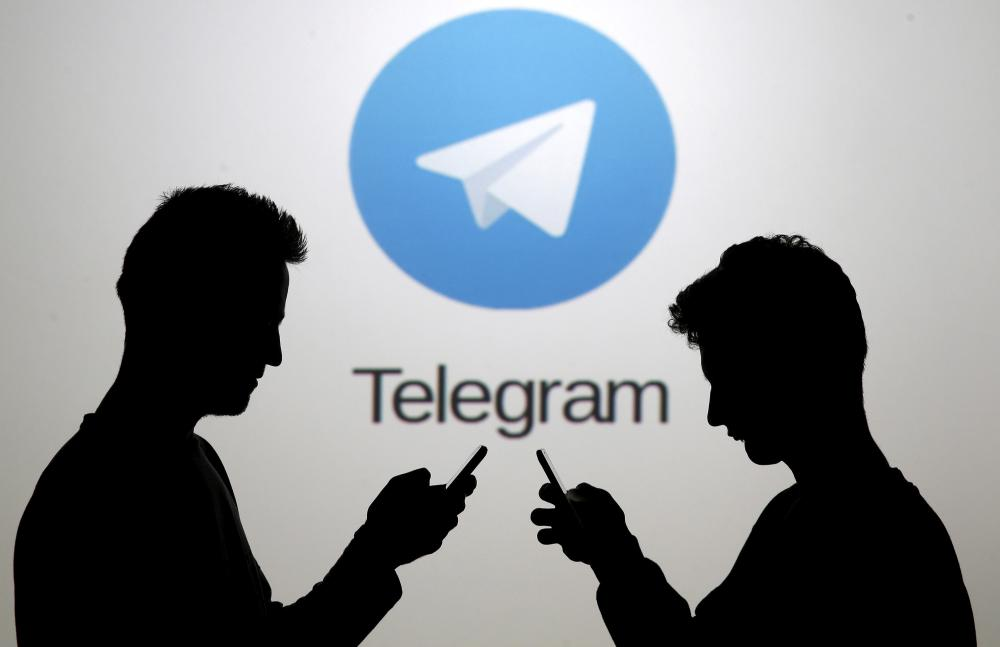 Men pose with smartphones in front of a screen showing the Telegram logo in this picture illustration. — Reuters