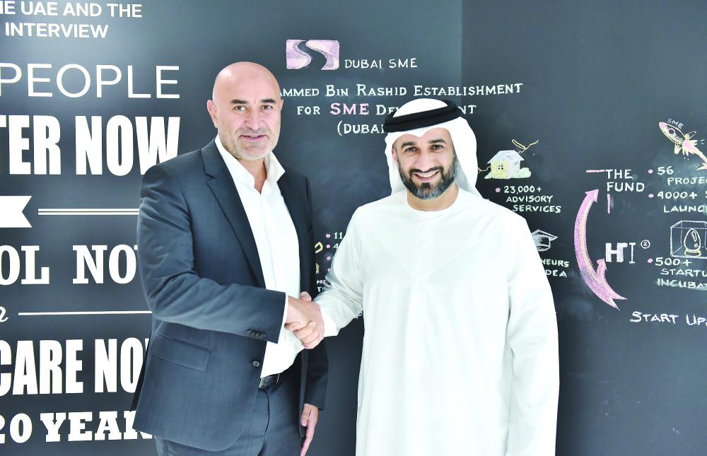 Abdul Basset Al Janahi, CEO of Dubai SME and Ronaldo Mouchawar, CEO and Co-Founder of Souq.com sign the MoU in the presence of senior executives from both sides