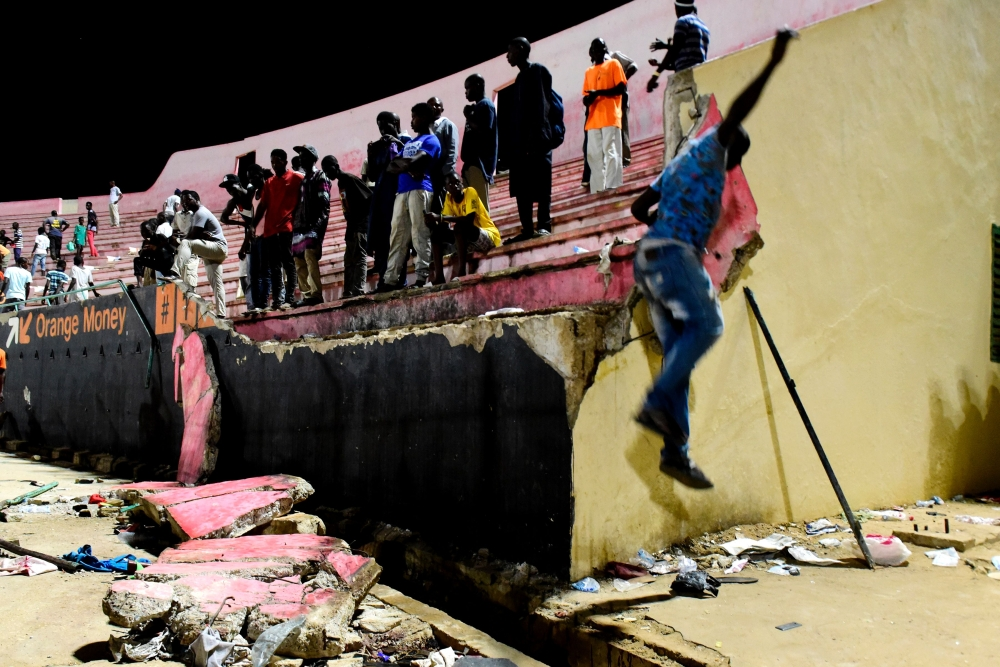 People look at the scene after a wall collapsed at Demba Diop stadium in Dakar after a football game between local teams Ouakam and Stade de Mbour on Saturday. — AFP