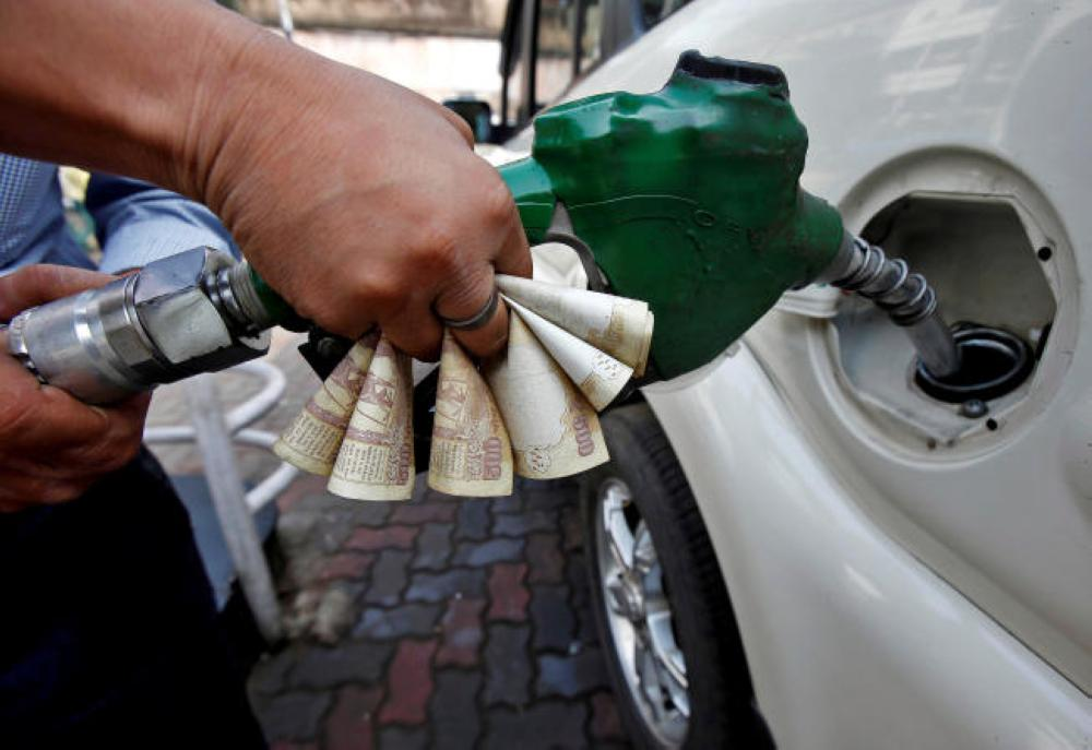 A worker fills diesel in a car as he holds 500 Indian rupee banknotes at a fuel station in Kolkata in this Nov. 9, 2016 file photo. — Reuters