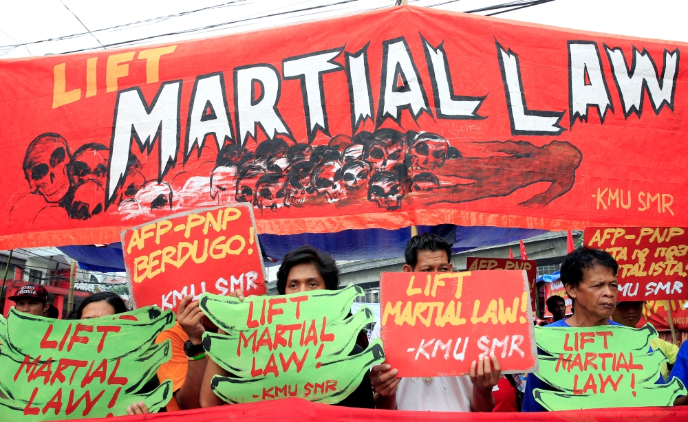 Activists display placards calling for lifting of martial law in the southern Philippines during a protest outside the presidential palace in Manila on Tuesday. — Reuters