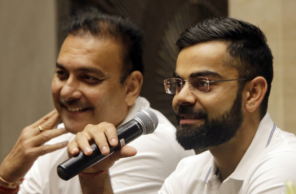 Indian cricket team captain Virat Kohli speaks as head coach Ravi Shastri reacts during a press conference before leaving for their Sri Lanka tour in Mumbai, India, Wednesday. — AP