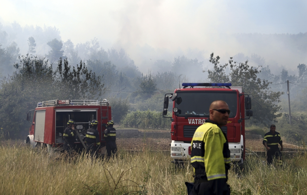 Firefighters gather near their trucks after controlling a fire in the village of Srinjine, southern Croatia, on Tuesday. — AP