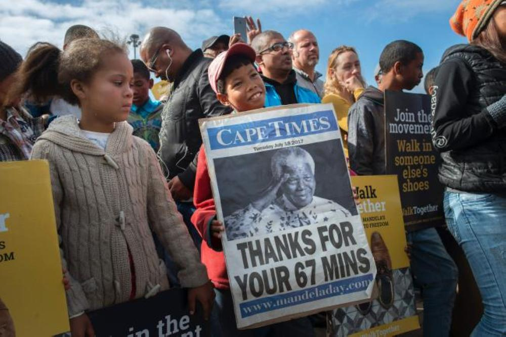 A young boy holds a poster with a photo of former South African President and Nobel Peace Prize laureate, Nelson Mandela, during Mandela Day, commemorating Mandela's birthday and his initiative against poverty, in Cape Town, South Africa, on Tuesday. — AFP