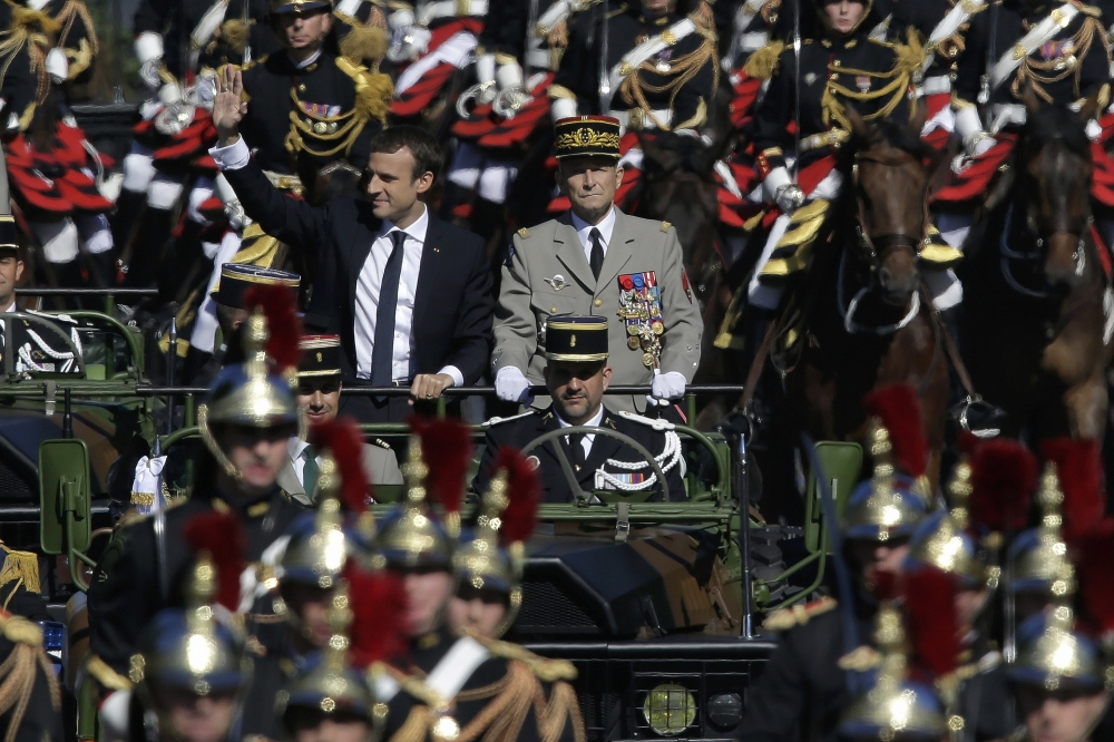 French President Emmanuel Macron, left, and chief of the Defense Staff Gen. Pierre de Villiers, right, drive down the Champs Elysees avenue during Bastille Day parade in Paris in this July 14, 2017 file photo. — AP
