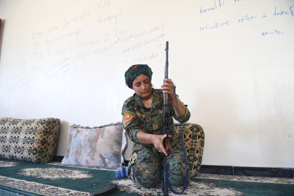Heza, a member of the Shengal Women's Units (YPS), a group of women fighters from Iraq's northeastern Sinjar region supporting the Women's Protection Units (YPG), prepares her rifle on the eastern outskirts of Raqqa, during the ongoing offensive by the Syrian Democratic Forces to retake the city from Daesh fighters. — AFP