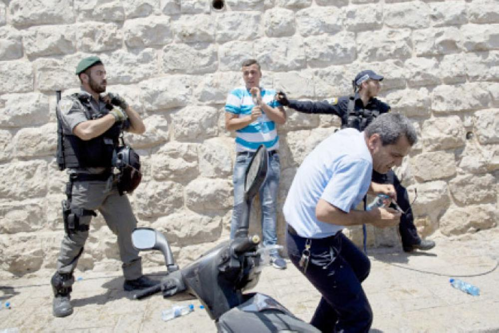 Israeli police officers clash with Palestinians outside the Lion's Gate in occupied Jerusalem's Old City, Wednesday. A dispute over metal detectors has escalated into a new showdown between Israel and the Muslim world. — AP