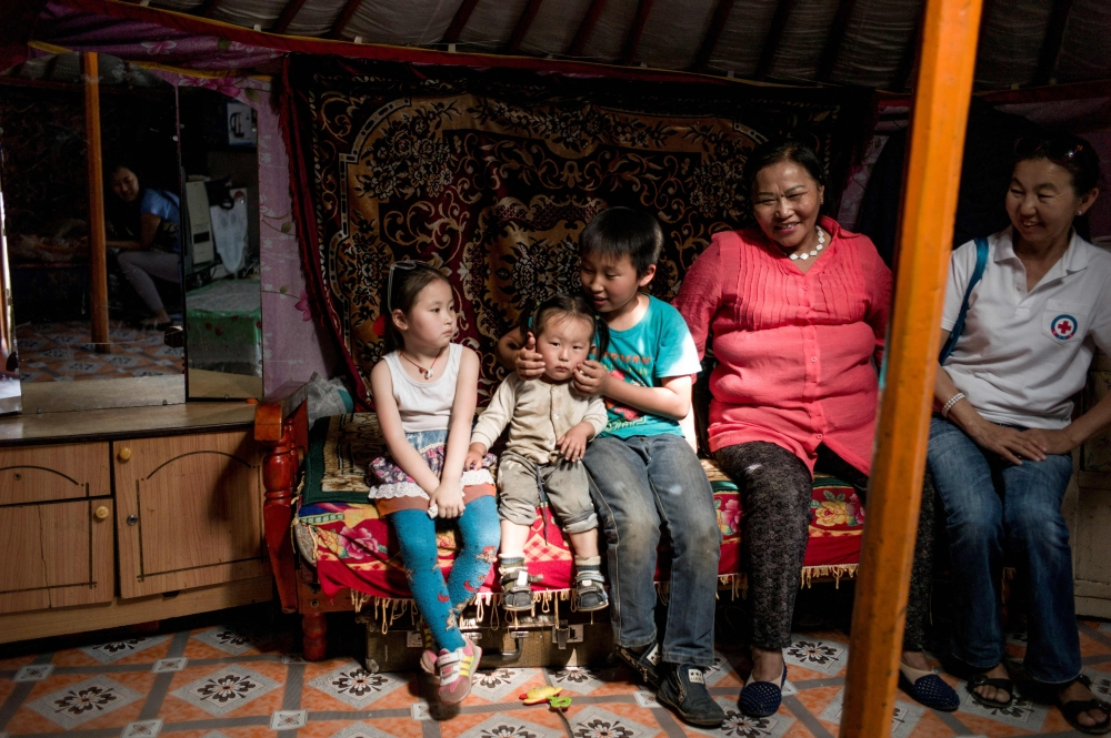 This photo taken on June 24, 2017 shows a family resting in a yurt, a traditional Mongolian house, on the outskirts of Ulan Bator. On the steep hills encircling Mongolia's capital, skyscrapers and apartments give way to ramshackle bungalows and tattered yurts, in rickety fenced enclosures with no running water - it is home to many of the landlocked country's nomadic herders, who migrated here in search of a better life. - AFP