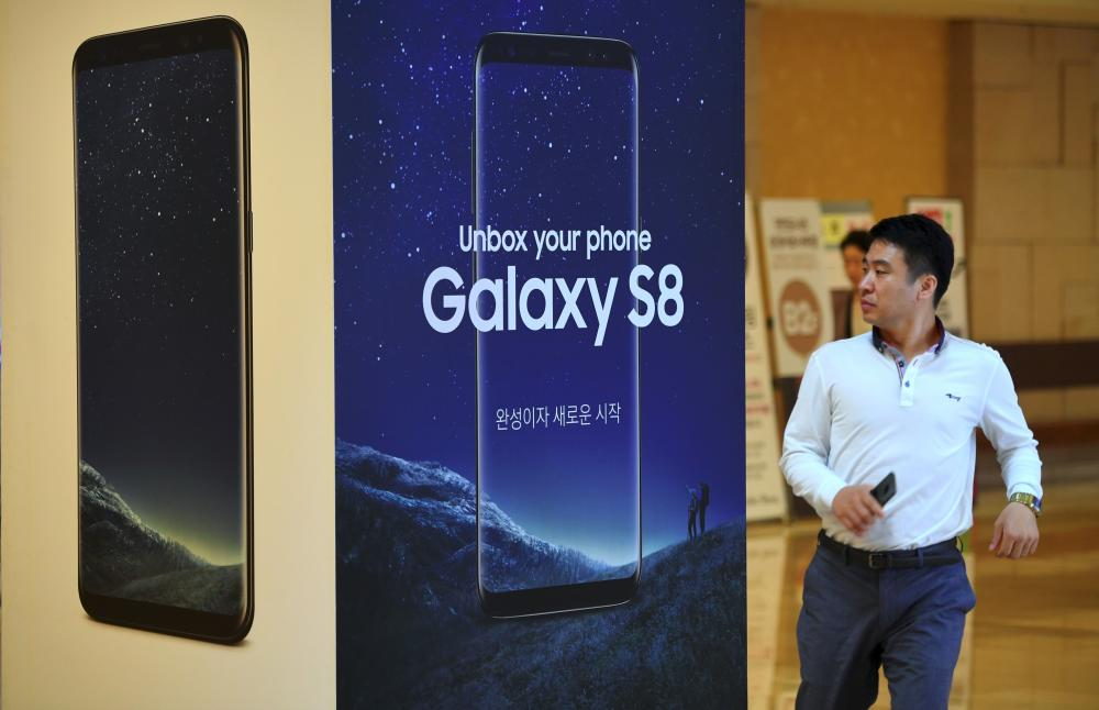 A man walks past an advertisement for the Samsung Galaxy S8 at the company's showroom in Seoul. — AFP