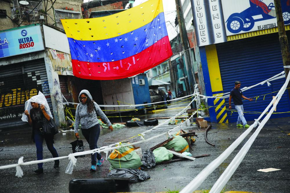 Pedestrians walk past a barricade during a rally in Caracas. — Reuters