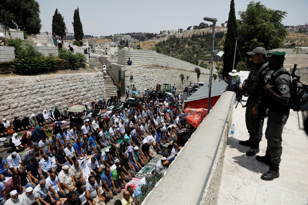 Israeli border police officers stand guard as Palestinians pray at Lions' Gate, the entrance to Jerusalem's Old City, in protest over Israel's new security measures at the compound housing Al-Aqsa Mosque. — Reuters
