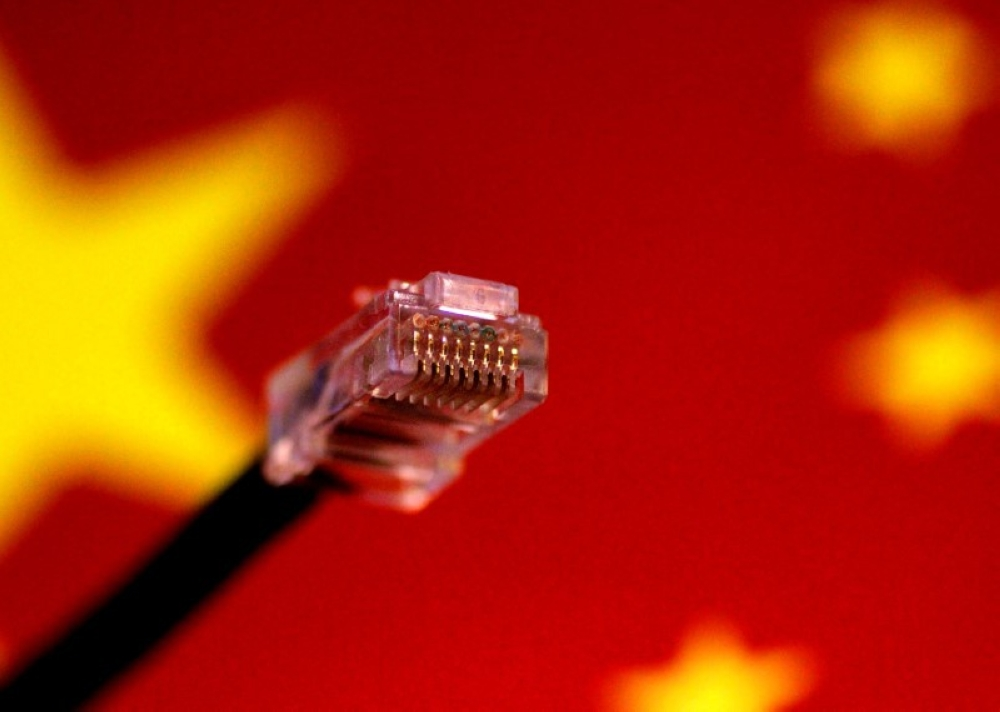 File photo of a computer network cable is seen above a Chinese flag.