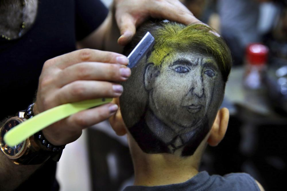 Muhannad Khaled Omar, right, prepares an image of US President Donald Trump on the back of a customer's head at his barber shop in Burj Al-Barajneh, southern Beirut, Lebanon. — AP