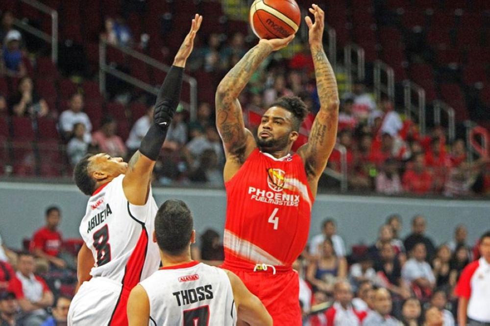 Phoenix import Eugene Phelps fires a jumper off the outstretched hand of Alaska's Calvin Abueva as Sonny Thoss looks on during their PBA Governor's Cup game at the Mall of Asia Arena Saturday night.