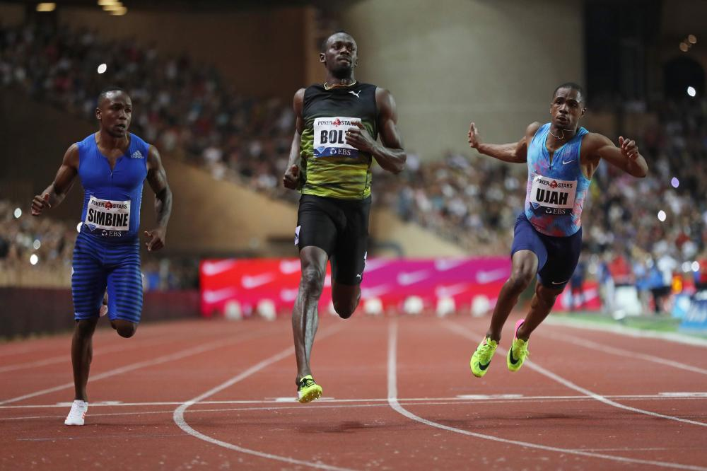 Jamaica's Usain Bolt (C) crosses the finish line to win the men's 100m event at the IAAF Diamond League athletics meeting in Monaco Friday. — AFP