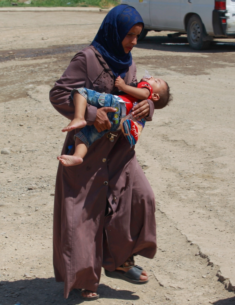 An Iraqi woman holds her baby as she walks towards the floating bridge between east and west of Mosul. — Reuters