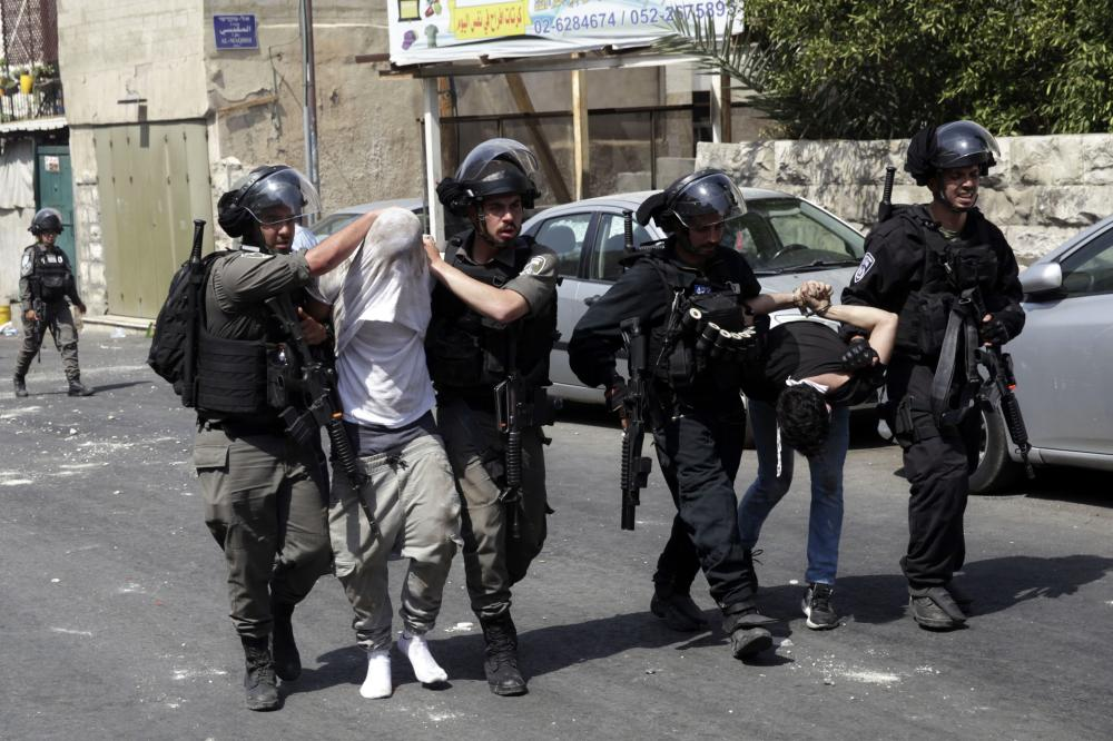 Israeli border police officers detain Palestinians during clashes in occupied Jerusalem. — AP