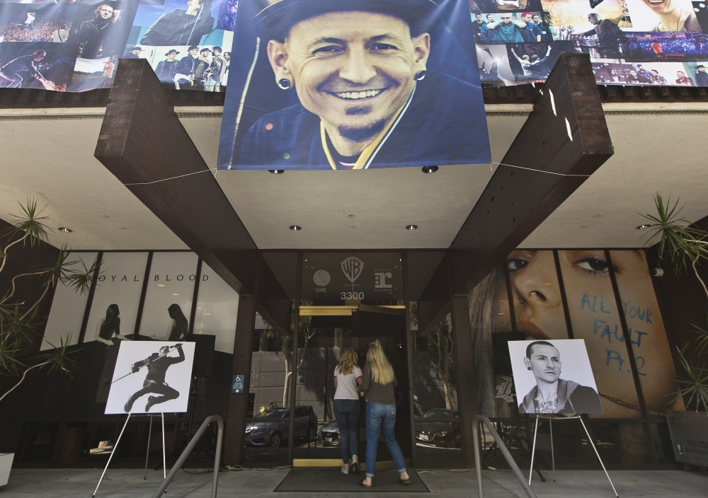 Banners showing photographs of singer Chester Bennington are displayed on the front of the Warner Bros. Records offices in Burbank, California on Saturday. - AP
