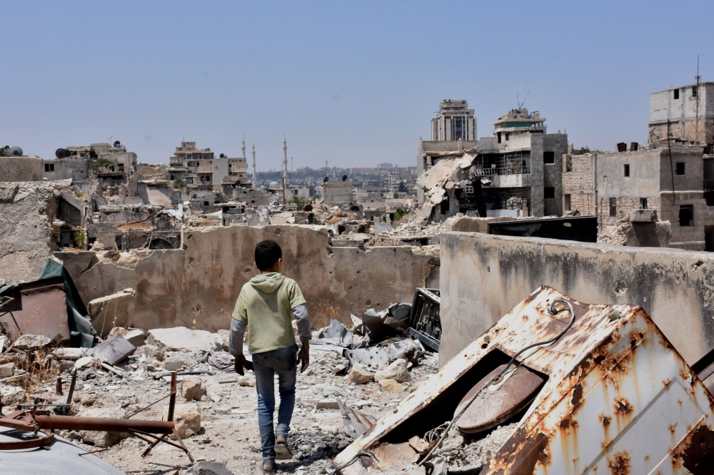 A Syrian boy walks amid the rubble of destroyed buildings in the northern city of Aleppo. — AFP