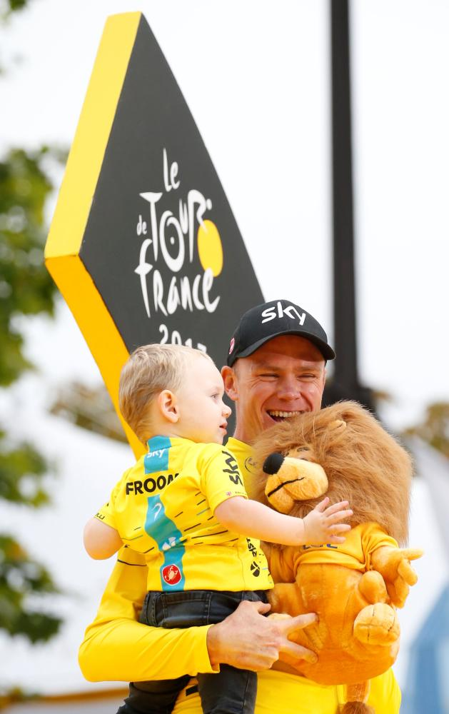 Team Sky rider Chris Froome of Britain celebrates his fourth Tour de France title with his son Kellan at Champs-Elysees, France, Sunday. — Reuters