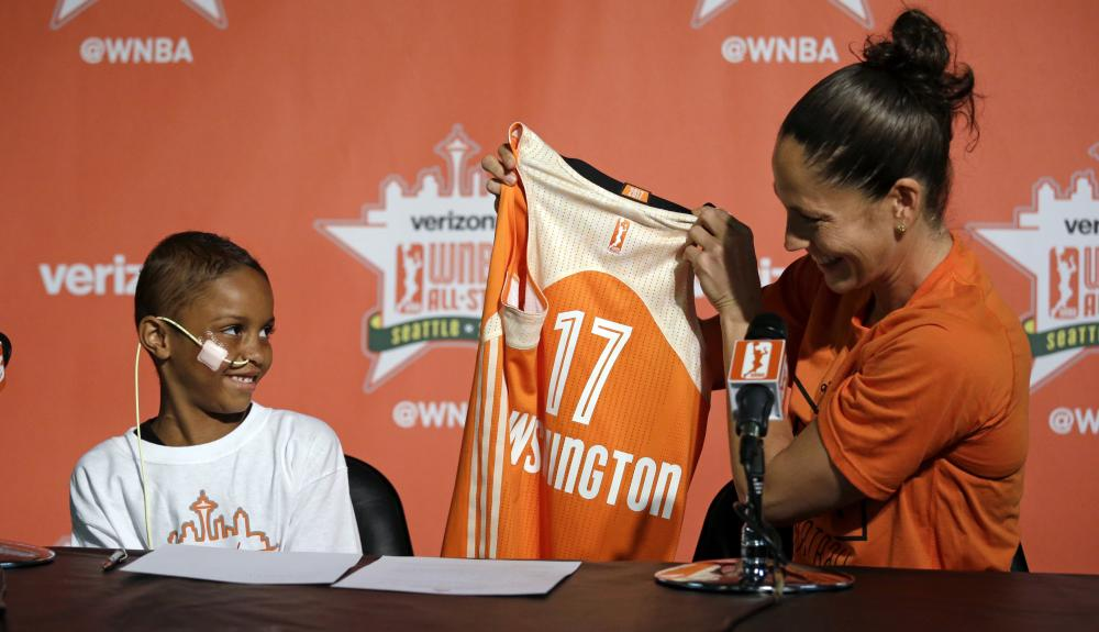 "Seattle Storm guard Sue Bird, right, holds up a jersey for Eniyah Washington, 6, after Bird signed the youngster to a WNBA All-Star basketball ""contract"" for the Western Conference team, through the Austen Everett Foundation, in Seattle. — AP"