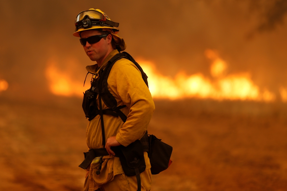 A firefighter stands near a grass fire as he prepares to defend a home from the Detwiler fire in Mariposa, California on Saturday. - Reuters