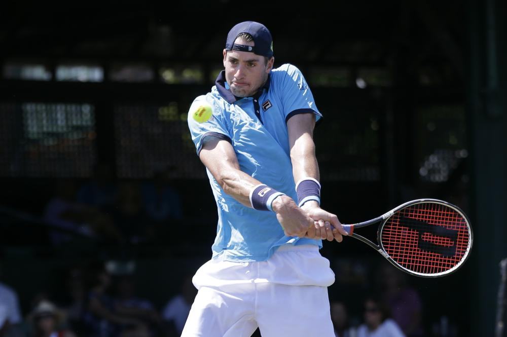 Top seed John Isner returns the ball to Dennis Novikov in their quarterfinal match at the Hall of Fame Tennis Championshipsin Newport, R.I. — AP