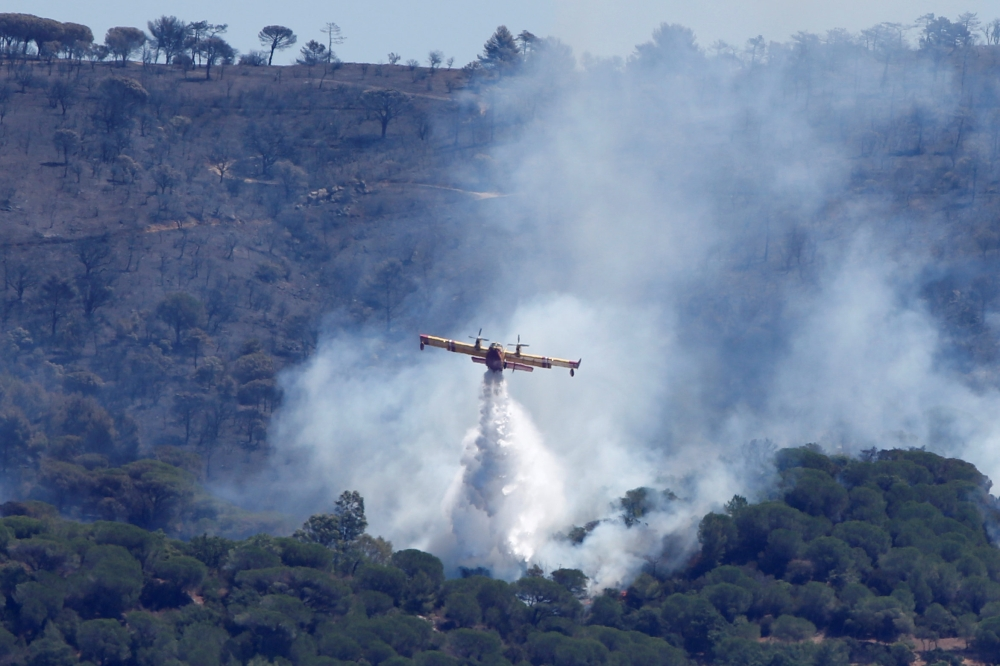 A Canadair firefighting plane drops water to extinguish a forest fire on La Croix-Valmer from Cavalaire-sur-Mer, near Saint-Tropez, France, on Tuesday. — Reuters