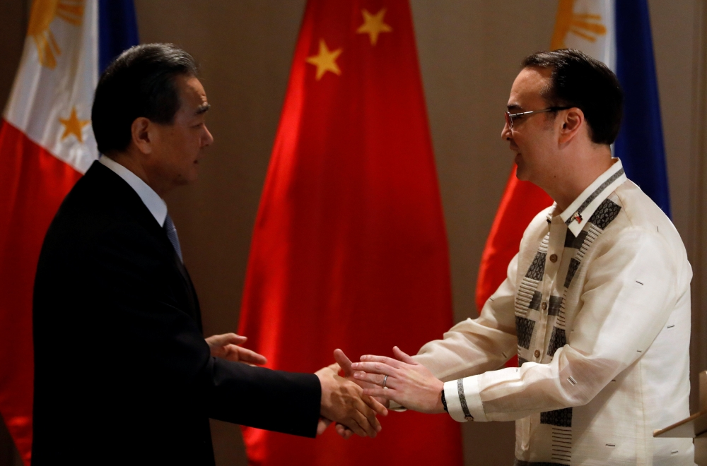 Philippine Foreign Affairs Secretary Alan Peter Cayetano, right, shakes hands with China's Foreign Minister Wang Yi in Taguig, Metro Manila, Philippines, on Tuesday. — Reuters