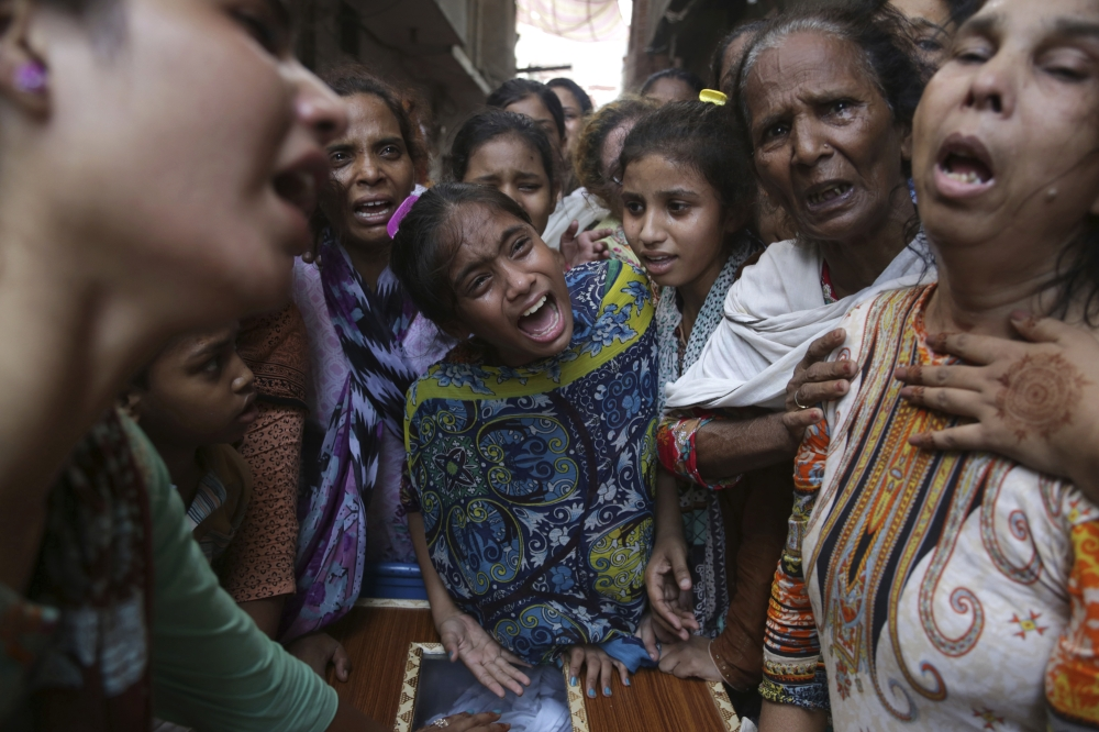 Pakistani relatives of suicide bombing victim mourn during a funeral in Lahore, Pakistan, on Tuesday. — AP