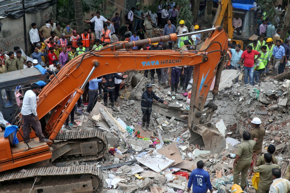Firefighters and rescue workers remove the debris as they search for survivors at the site of a collapsed building in the suburbs of Mumbai, India, on Tuesday. — Reuters