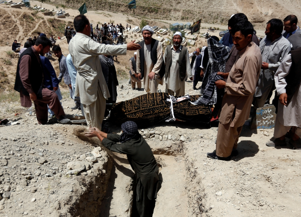 Relatives take part in a burial ceremony of the victims of Monday's suicide attack in Kabul, Afghanistan, on Tuesday. — Reuters