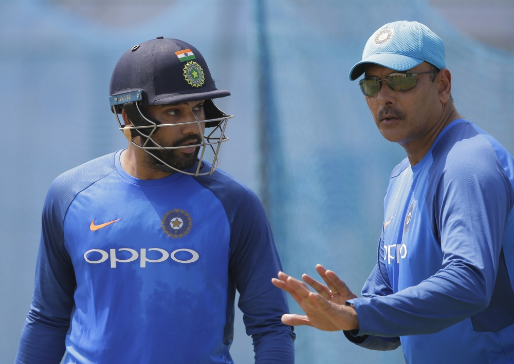 India's batsman Rohit Sharma, left, listens to head coach Ravi Shastri during a training session ahead of the first Test cricket match against Sri Lanka in Galle, Sri Lanka, Tuesday. — AP