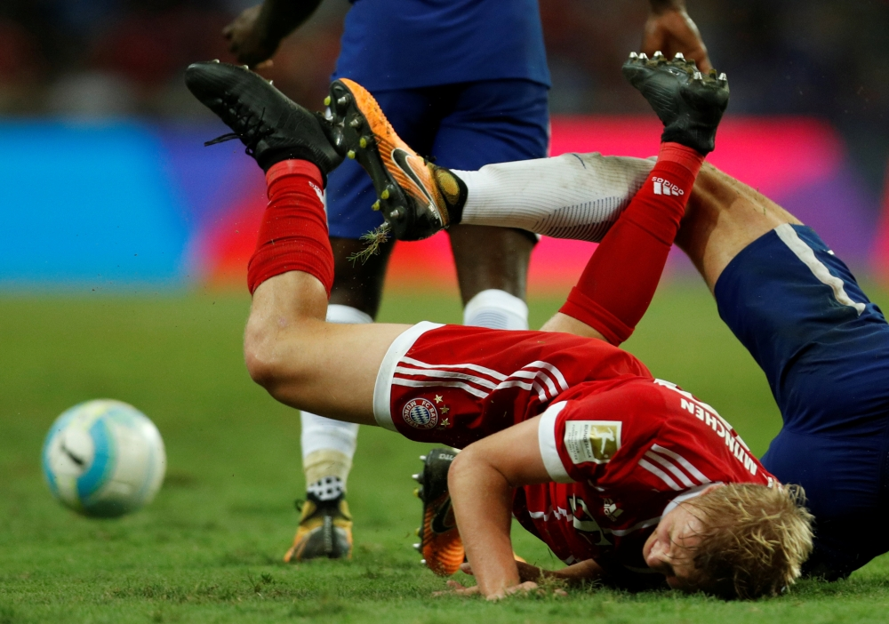 Bayern Munich's Felix Gotze is brought down by a Chelsea defender's tackle during the International Champions Cup match at the National Stadium, Singapore, on Tuesday. — Reuters