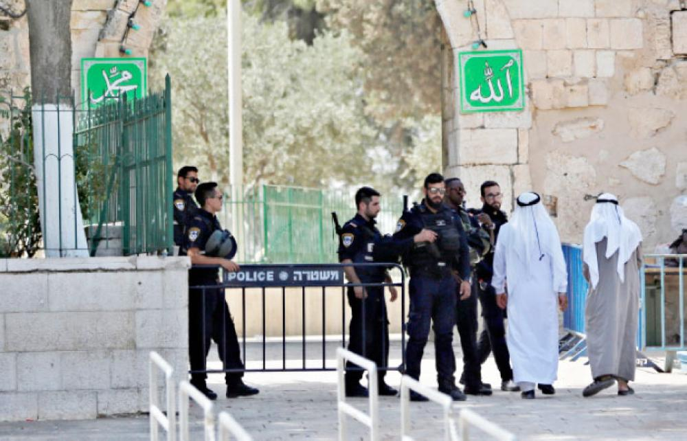 Palestinians walk next to Israeli security forces at the entrance of Al-Aqsa Mosque compound on Tuesday morning after Israel removed metal detectors. — Reuters