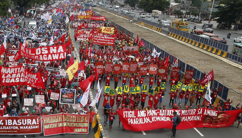 "Indigenous people known as Lumads, right, form the words ""Save Lumad schools"" as they join a march of thousands of protesters to coincide with the state of the nation address of Philippine President Rodrigo Duterte in Quezon city, northeast of Manila, in this July 24, 2017 file photo. — AP"