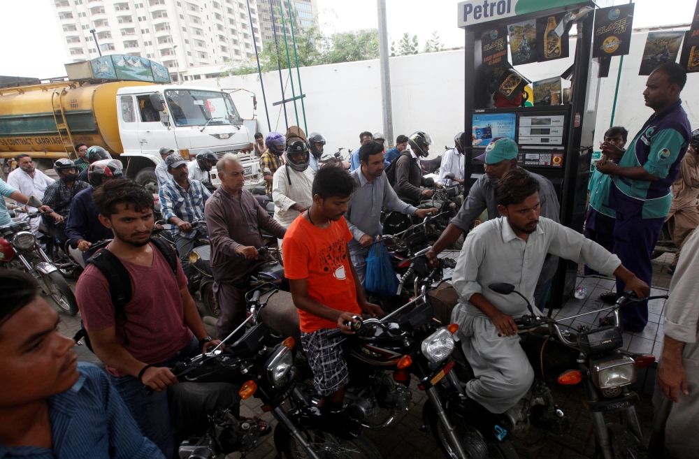 Customers buy petrol at a petrol station in Karachi, Pakistan, on Wednesday. — Reuters