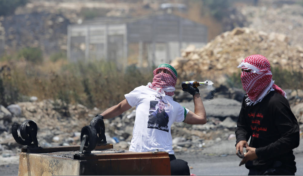 A Palestinian man throws a Molotov cocktail at Israeli soldiers during clashes in the west Bank city of Ramallah, this week.  — AP