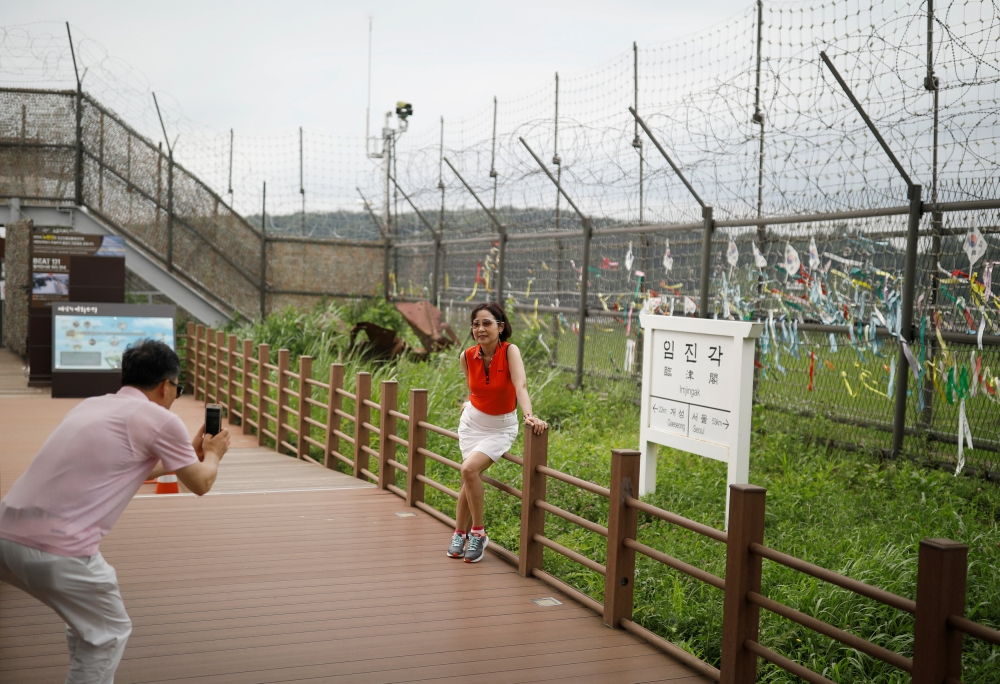 A woman poses for photographs in front of a barbed-wire fence near the demilitarized zone separating the two Koreas in Paju, South Korea. - Reuters