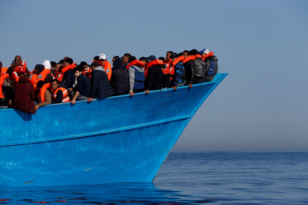 Migrants on a wooden boat await rescue by the Malta-based NGO Migrant Offshore Aid Station (MOAS) in the central Mediterranean in international waters off the coast of Sabratha in Libya in this April 15, 2017 file photo. — Reuters