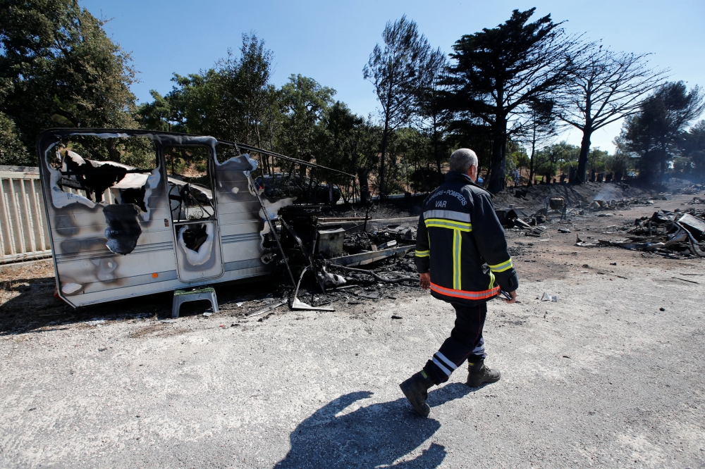 A fireman walks past charred debris of vehicles that were destroyed by fire in a parking lot for camping cars in Bormes-les-Mimosas, in the Var department, France, on Wednesday. — Reuters