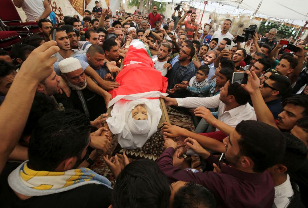 Mourners carry the body of 17-year-old Mohammad Jawawdah, who was killed on the weekend when he attacked a security guard at the Israeli embassy compound in the Jordanian capital with a screwdriver, during his funeral in Amman, Tuesday. — AFP