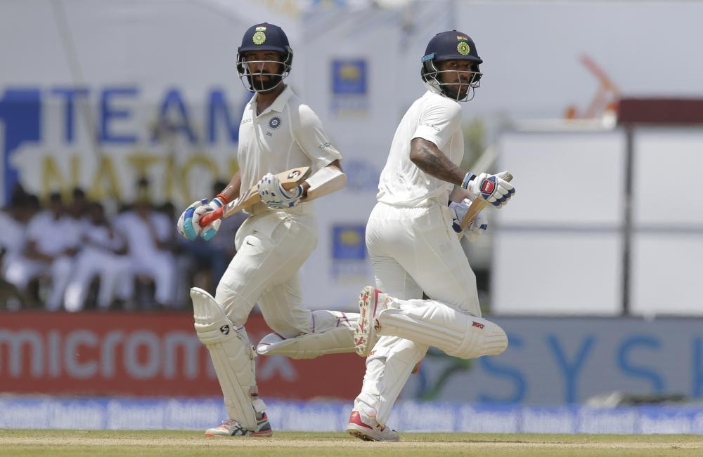 India's Cheteshwar Pujara (L) and Shikhar Dhawan run between wickets during the first day's play of the first Test cricket match against Sri Lanka in Galle, Sri Lanka, Wednesday. — AP