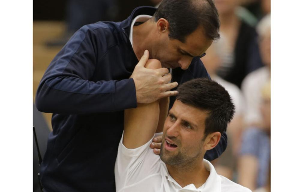 In this July 11, 2017 file photo Serbia's Novak Djokovic is receiving treatment from a trainer during a break at the Wimbledon Tennis Championships in London. — AP