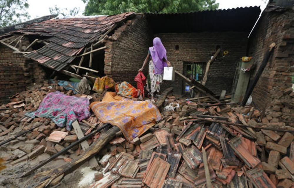 An Indian woman searches for belongings in the debris of her damaged house in a flood affected village near Thara in Banaskantha district, Gujarat, India Wednesday. — AP