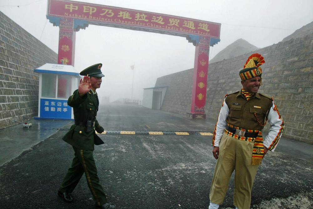 A Chinese soldier (left) waves next to a smiling Indian soldier at the Nathu La border crossing between India and China in India's northeastern state of Sikkim.  — AFP